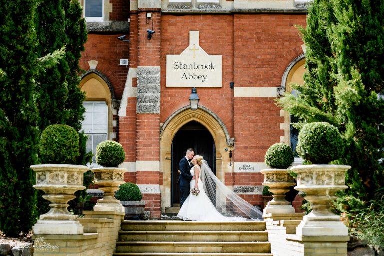 Bride and groom kiss outside entrance of Stanbrook Abbey in Worcestershire