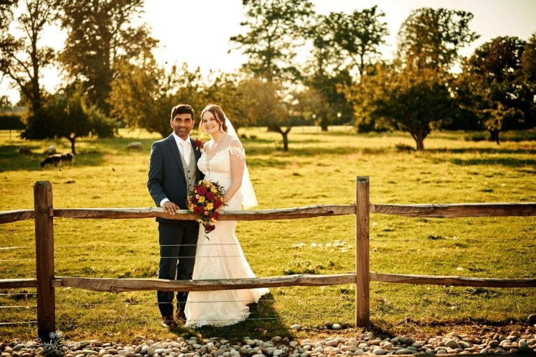 Bride and groom in meadow at Stanbrook Abbey with beautiful evening light