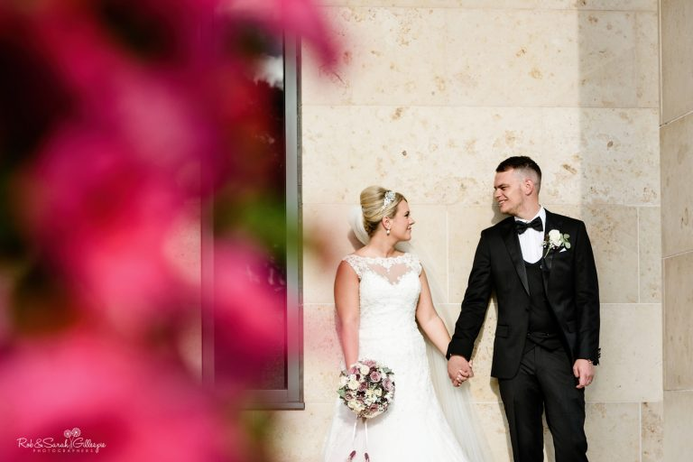 Bride and groom holding hands outside Stanbrook Abbey