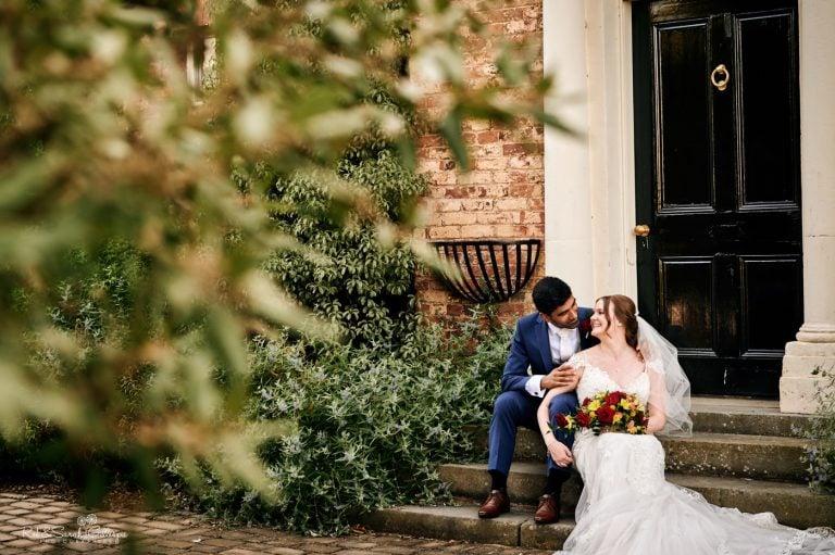 Bride and groom sit on steps