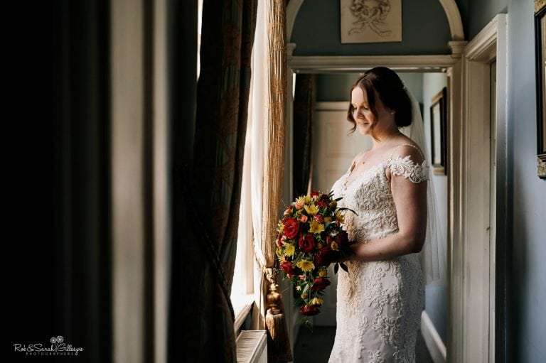 Portrait of bride with red and yellow bouquet in window light at Stanbrook Abbey