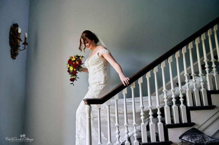 Bride in white wedding dress walks down staircase in Brides Manor at Stanbrook Abbry