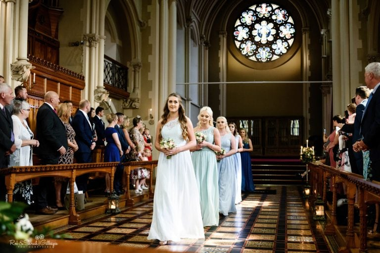 Five bridesmaids walk in line up aisle at Stanbrook Abbey wedding