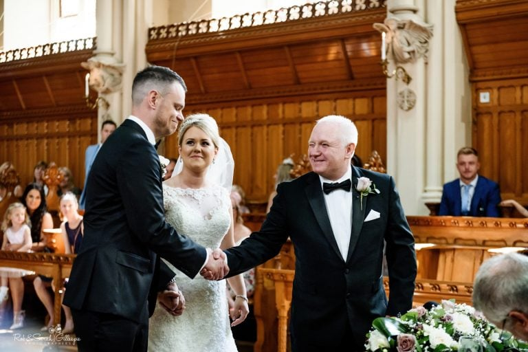 Bride's father gives her away during wedding ceremony in Callow Great Hall at Stanbrook Abbey