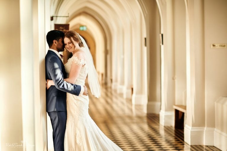 Bride and groom hug in cloister corridor at Stanbrook Abbey