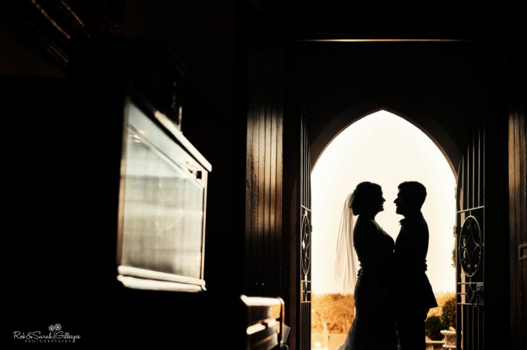 Silhouette of bride and groom in arched doorway at Stanbrook Abbey