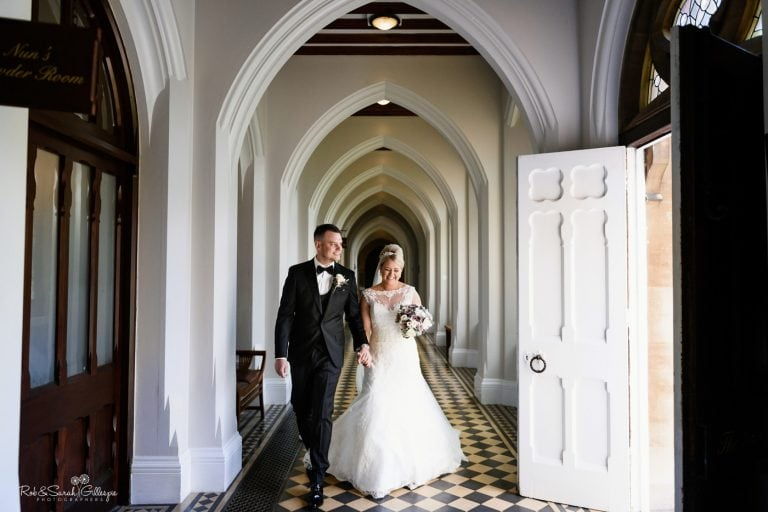Bride and groom relaxed and happy walking through cloister corridor at Stanbrook Abbey