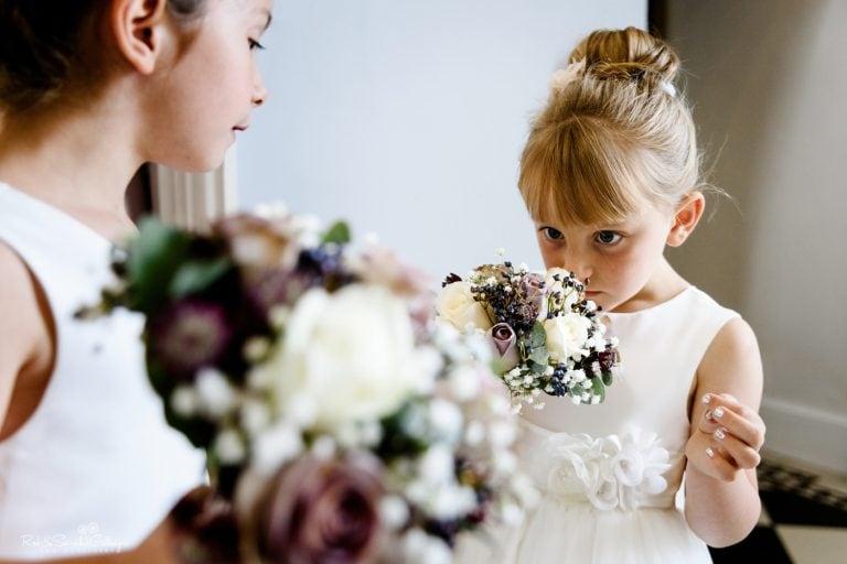 Young flowergirl sniffs her wedding bouquet