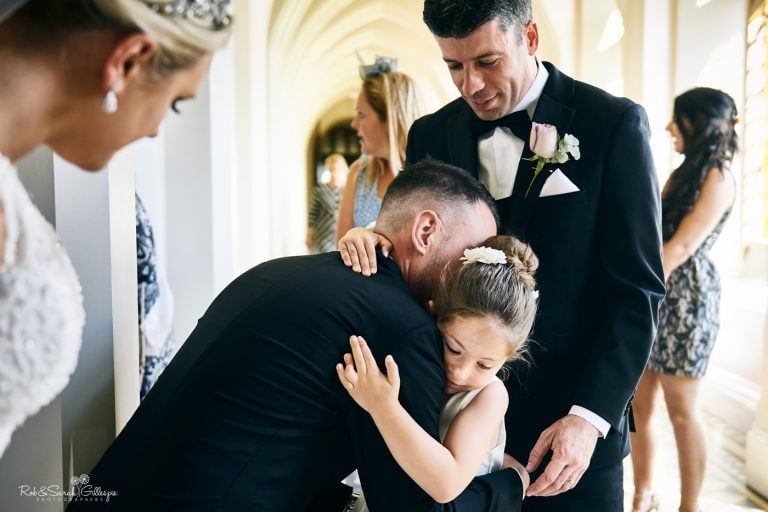 Young girl hugs groom at Stanbrook Abbey wedding