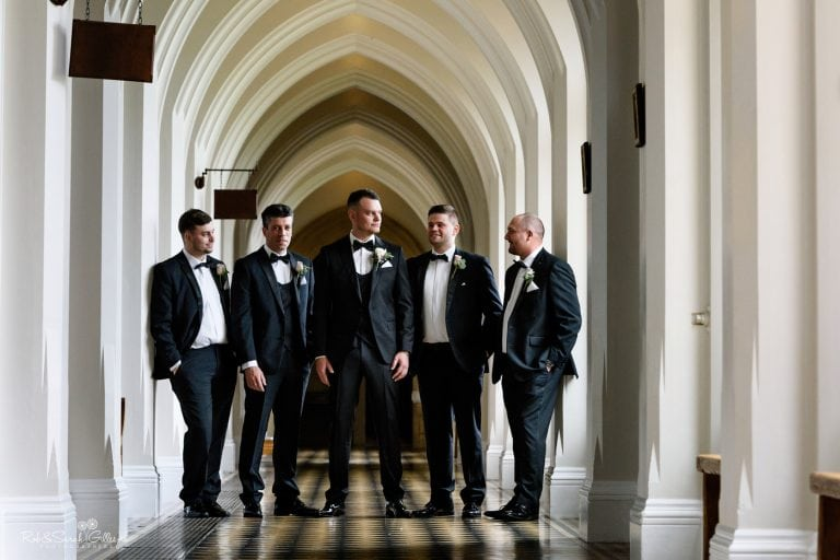 Group photo of groom and four groomsmen in cloister corridor at Stanbrook Abbey