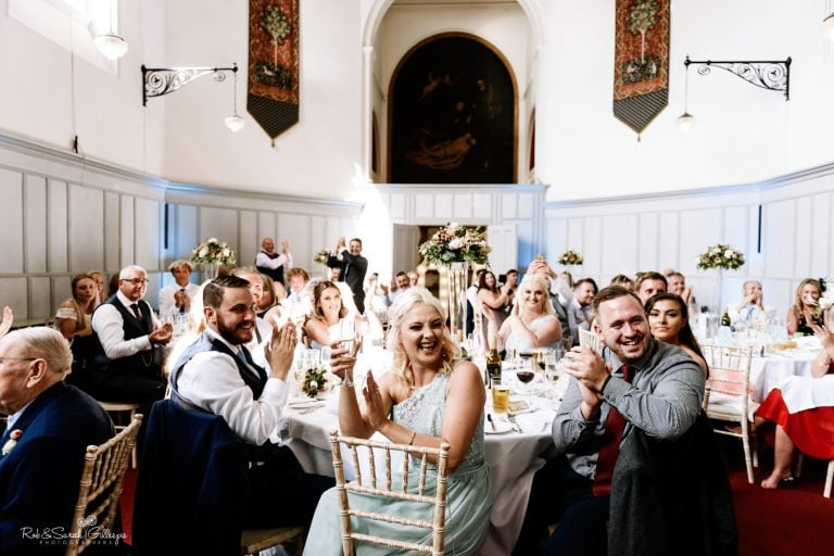 Wedding guests clapping at speeches inside St Annes Hall at Stanbrook Abbey
