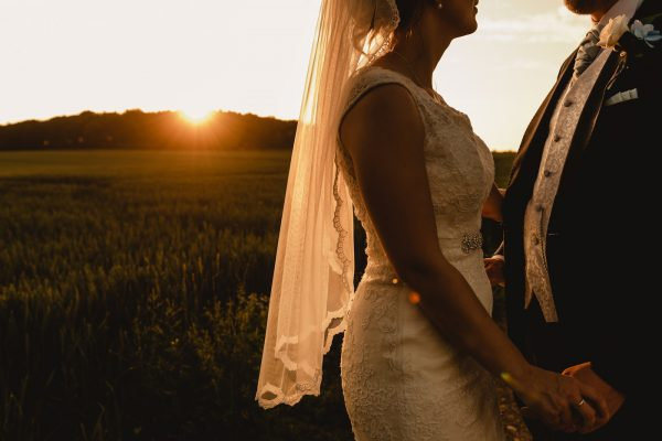 Bride and groom in wheat field on summer evening with beautiful sunset backlighting the veil