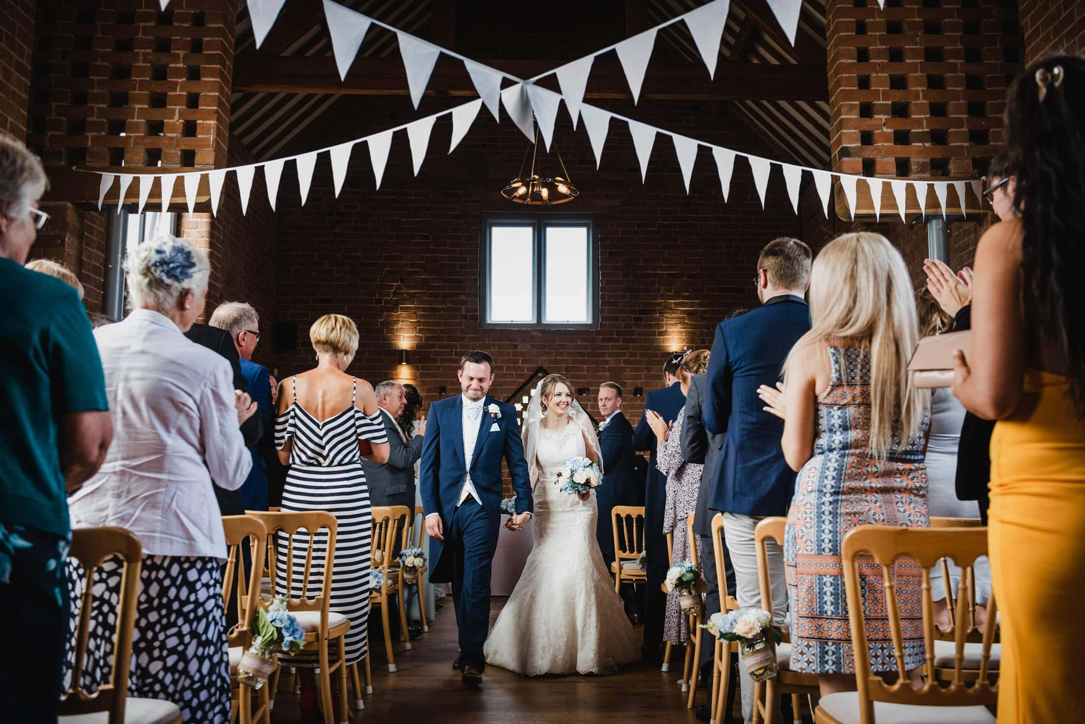 Newly married couple leave wedding ceremony inside old barn as guests clap