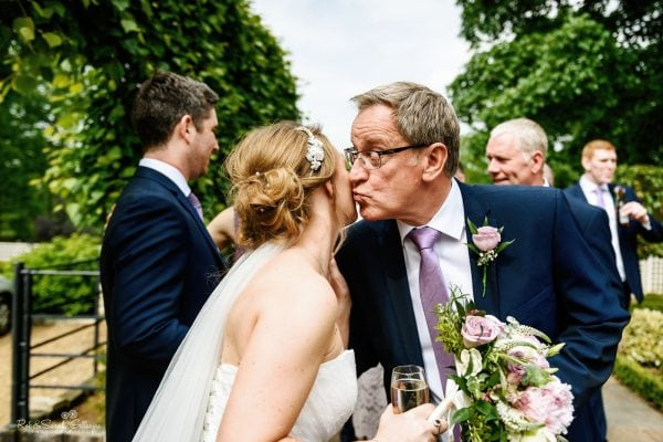 Bride and guest kiss after wedding ceremony