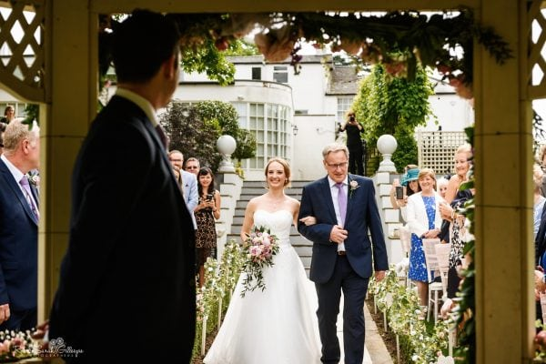 Bride smiles at groom as she walks up aisle during outdoor ceremony at Warwick House