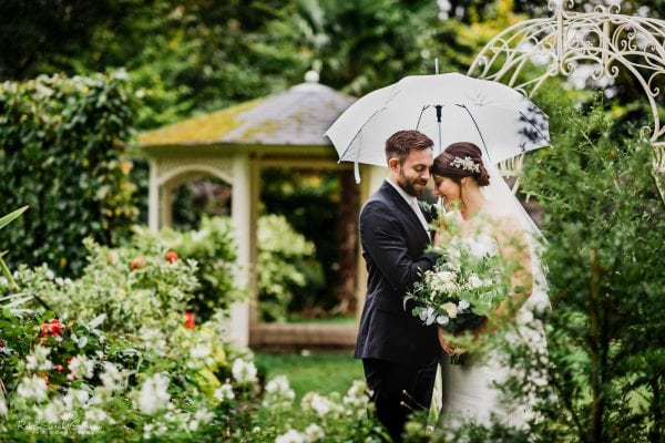 Bride and groom under white umbrella in gardens at Warwick House on rainy day