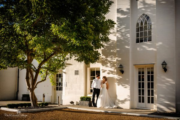 Bride and groom relax under tree at Warwick House in beautiful evening light