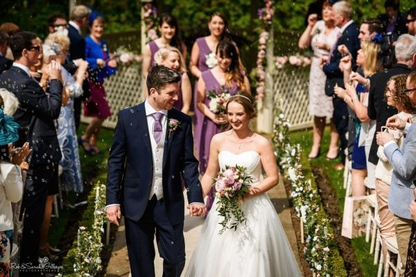 Bride and groom leave outdoor wedding ceremony as guests blow bubbles