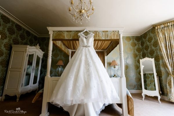 Wedding dress hanging on four-poster bed in beautiful room at Warwick House