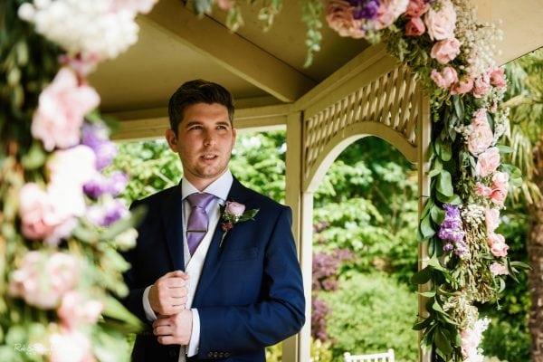 Groom waits under gazebo for bride to arrive