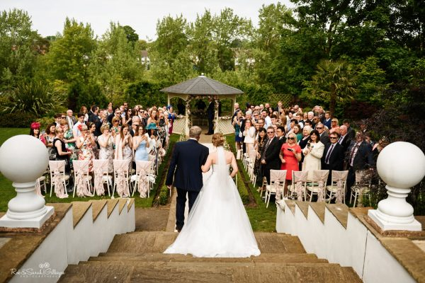 View from steps as bride and father walk up aisle at outdoor wedding ceremony