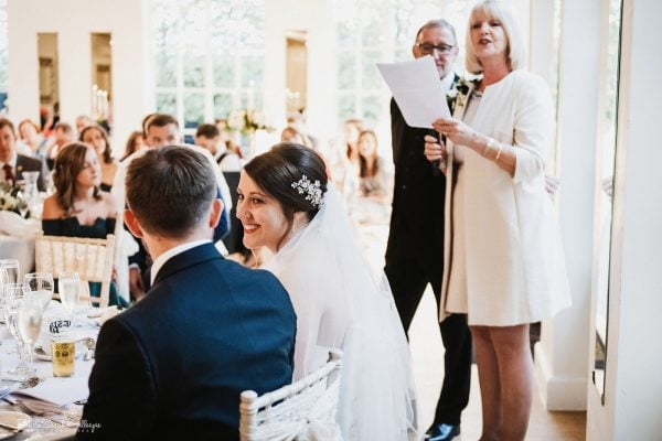 Bride smiles at groom as parents give wedding speech