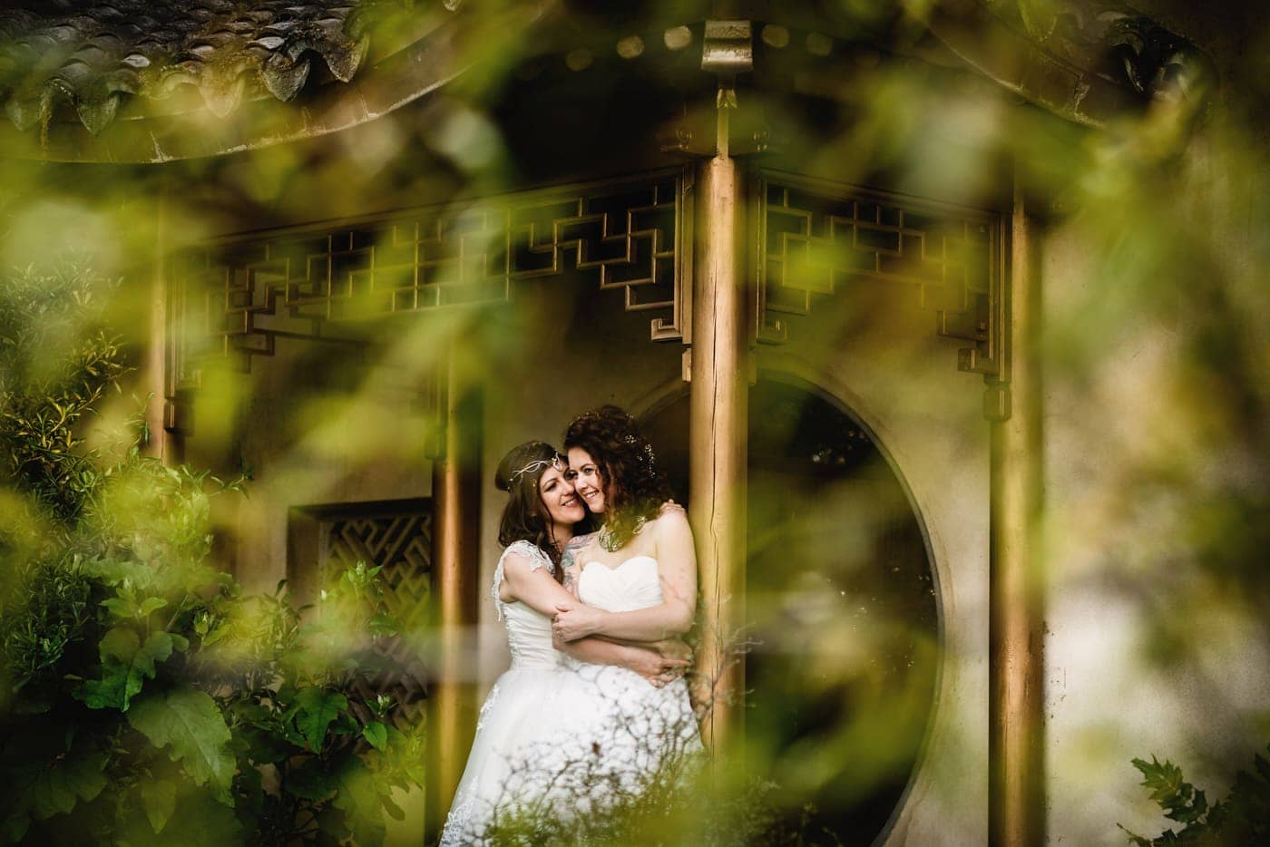 Two brides hugging under pagoda in beautiful gardens