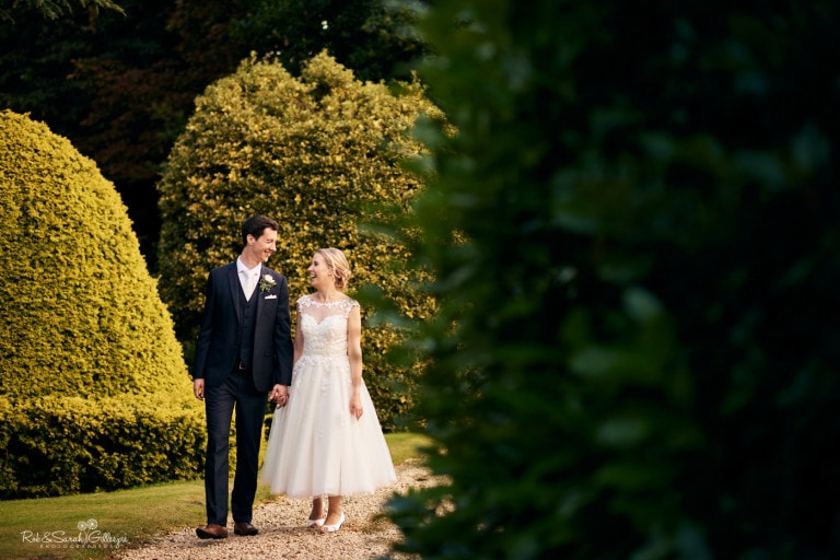 Bride and groom walking through gardens at Highbury Hall in Birmingham