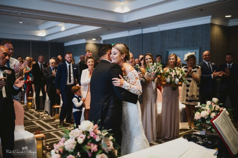 Bride and groom embrace during wedding ceremony at Birmingham Hyatt Regency hotel