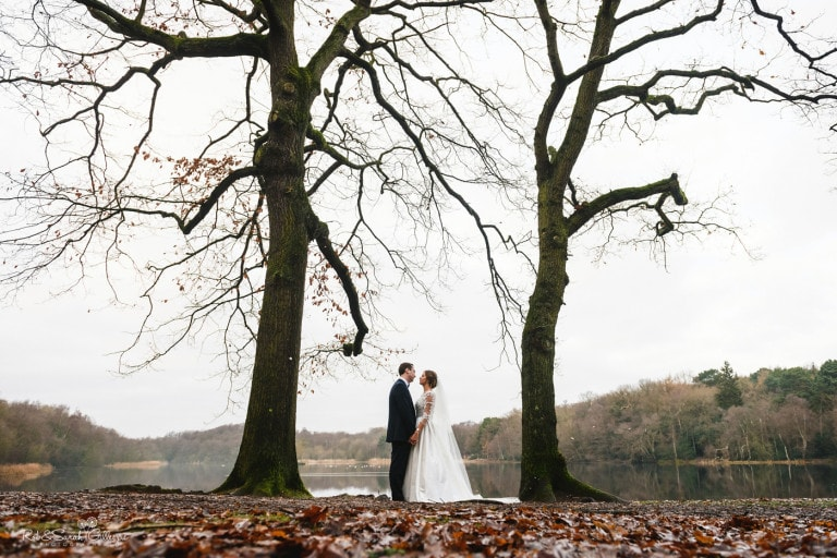 Bride and groom standing between two bare trees in Sutton Park in Birmingham