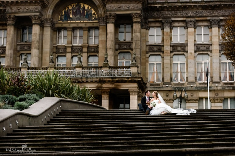 Newly married couple sitting on steps in front of Birmingham Council House