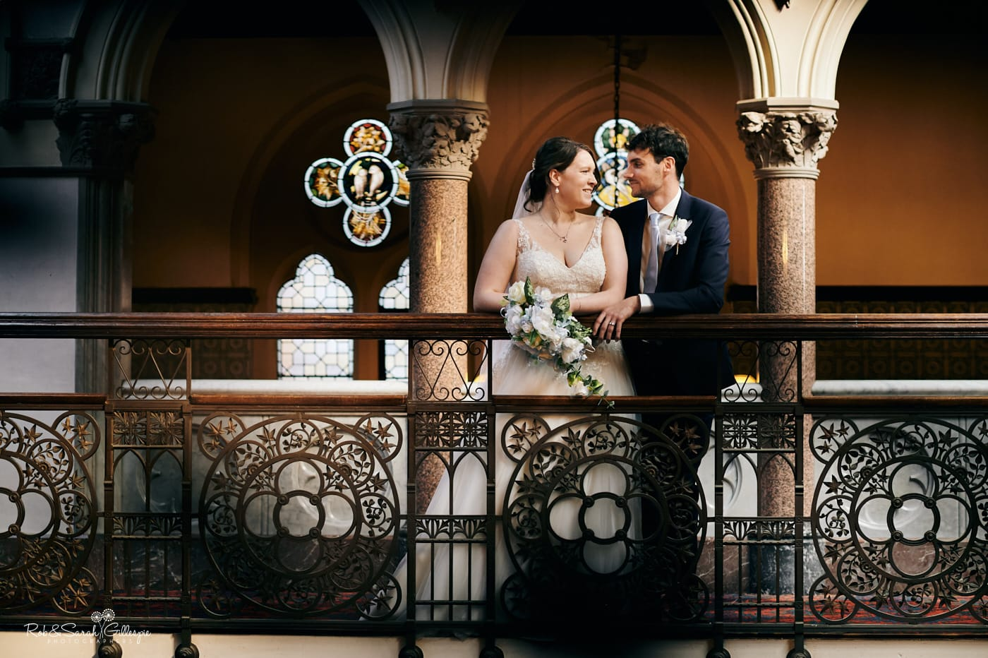 Bride and groom on balcony in beautiful old venue