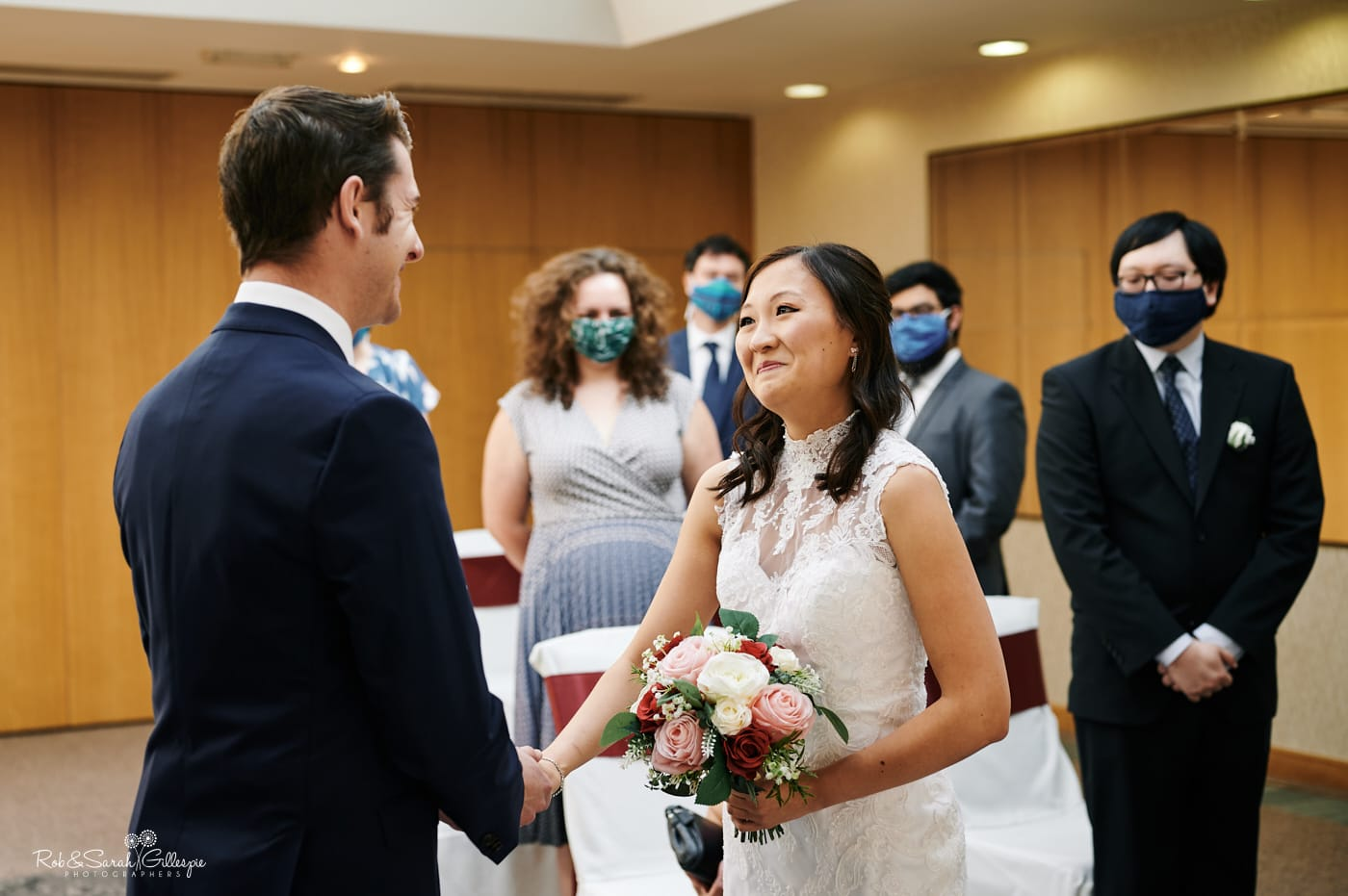 Bride and groom emotional as they exchange wedding vows as guests in facemasks watch