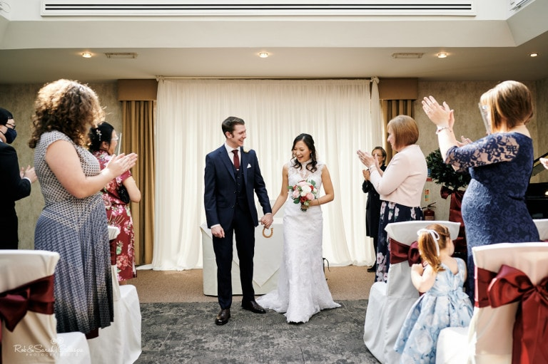 Bride and groom exit small ceremony as guests clap
