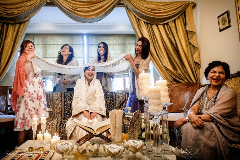 Bride and friends laughing at home wedding ceremony