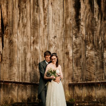 Bride and groom in front of large barn doors