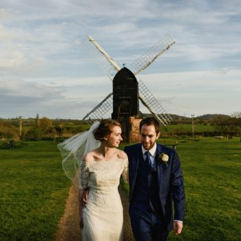 Bride and groom walk away from old windmill