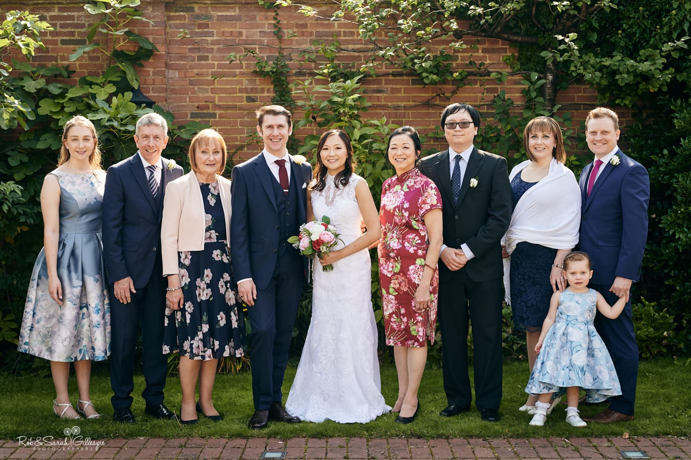 Small wedding family group photo in beautiful gardens