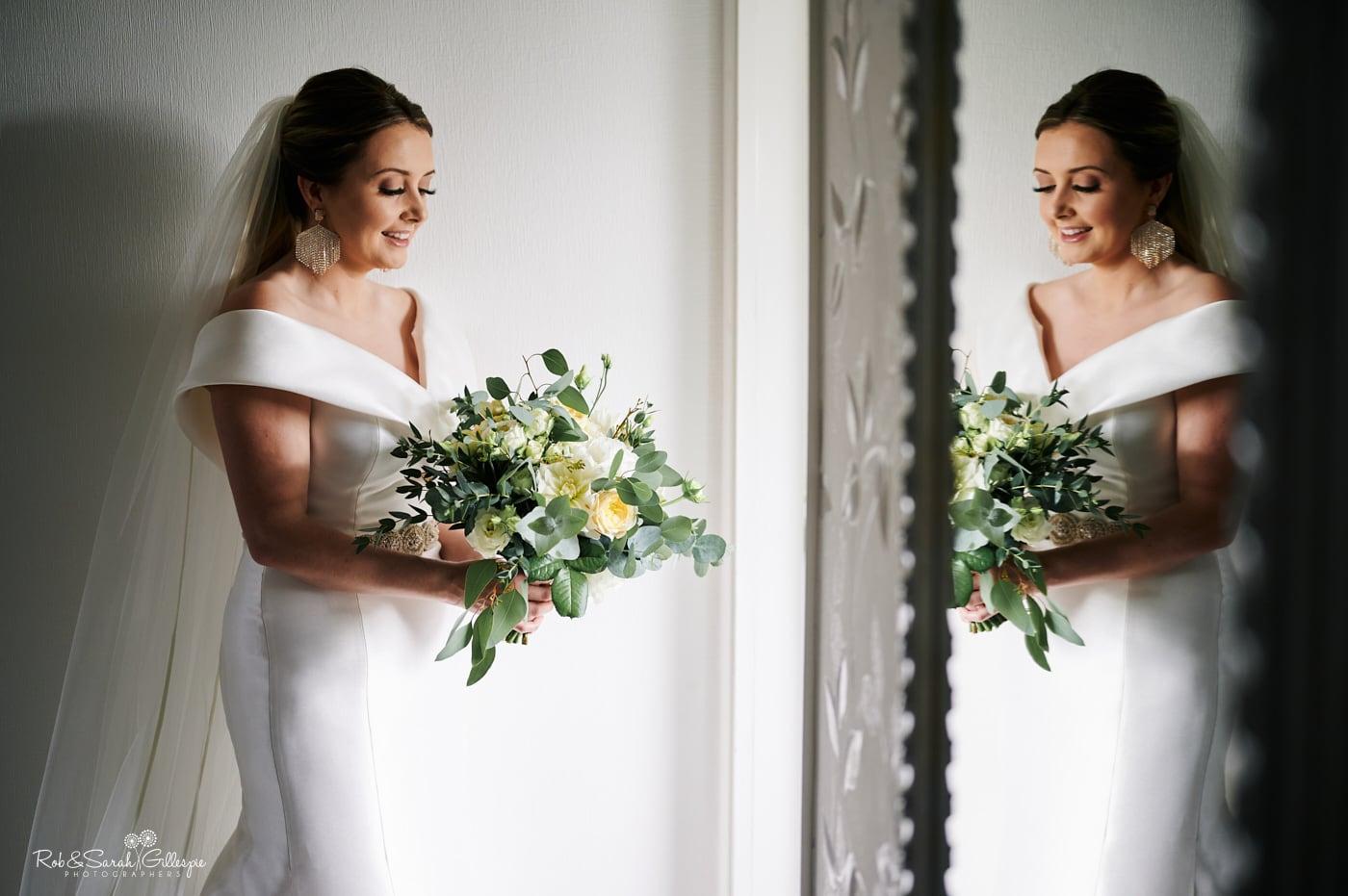 Beautiful portrait of bride in mirror holding bouquet