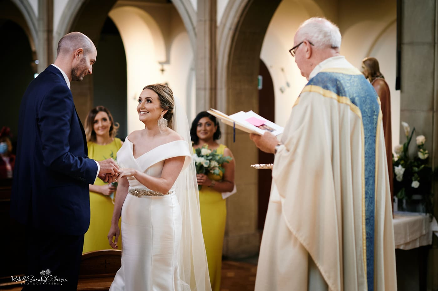 Bride and groom ring exchange during wedding ceremony in catholic church