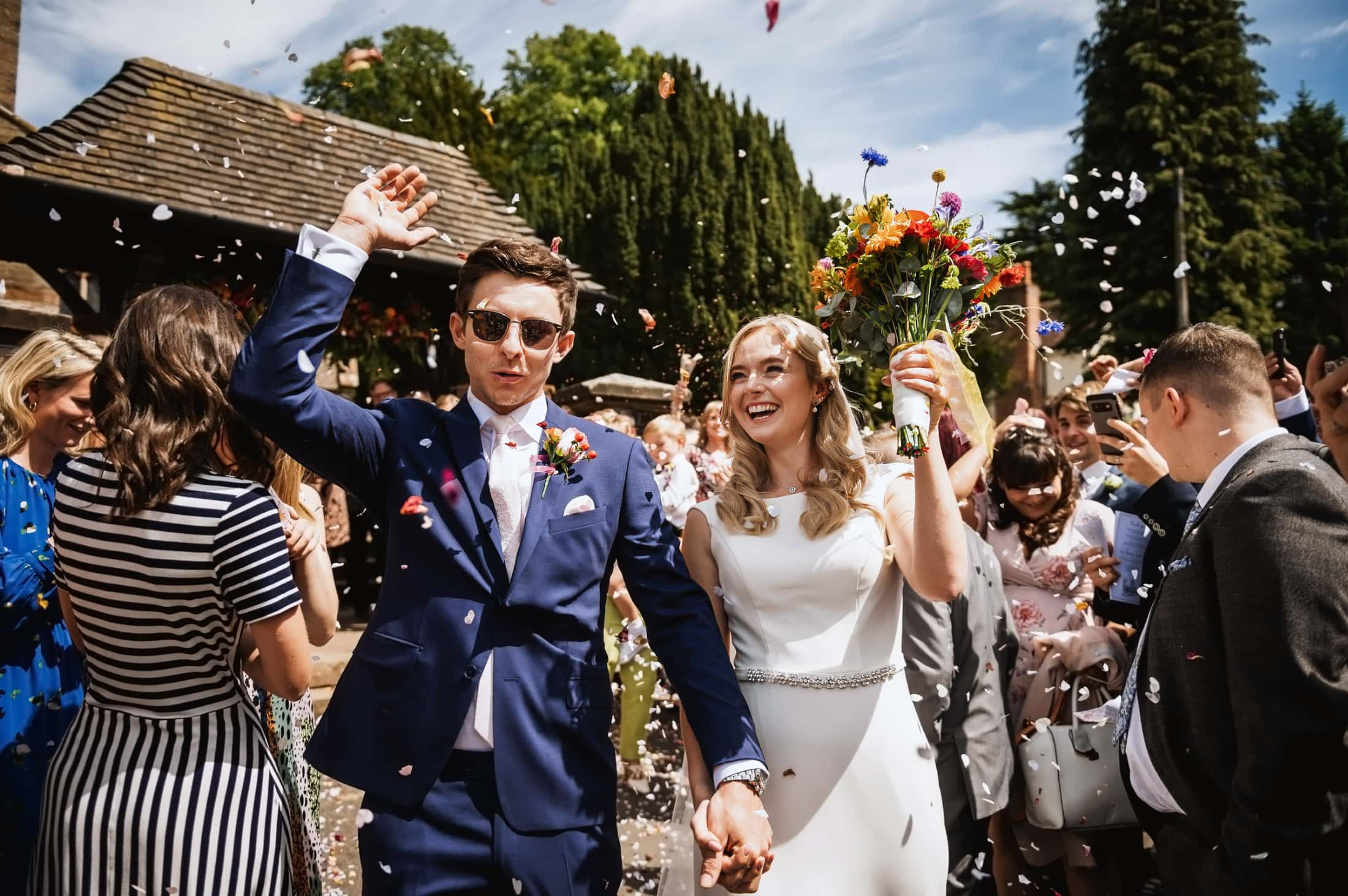 Bride and groom laughing as they walk through confetti after church ceremony