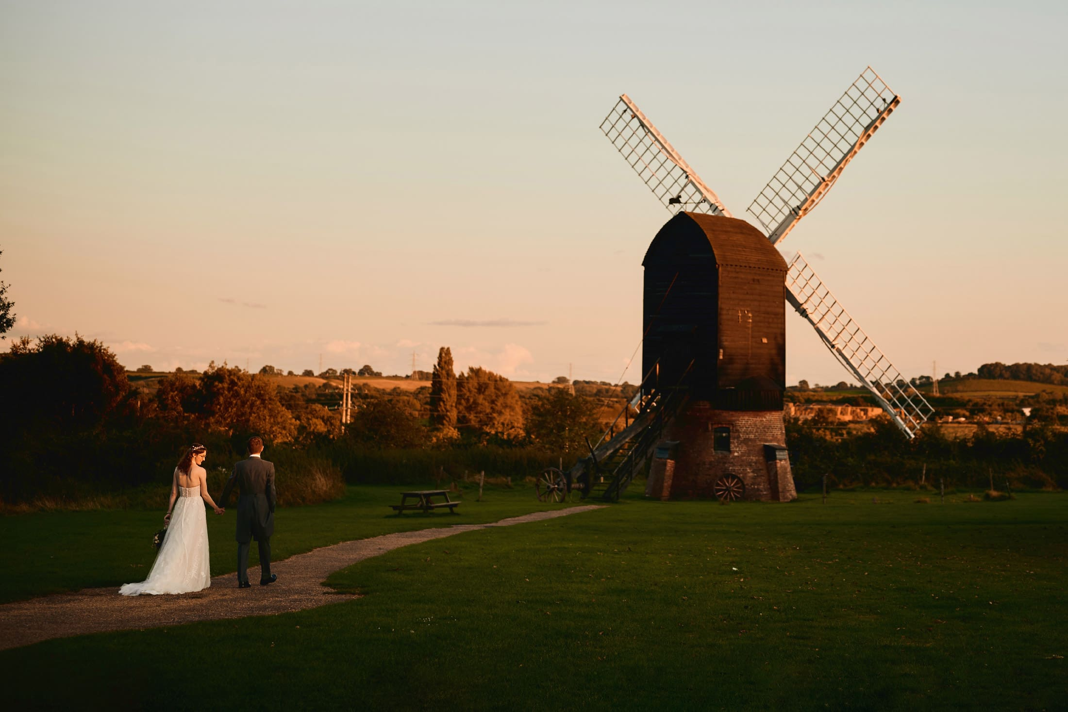 Bride and groom walk hand in hand towards old windmill in beautiful evening light