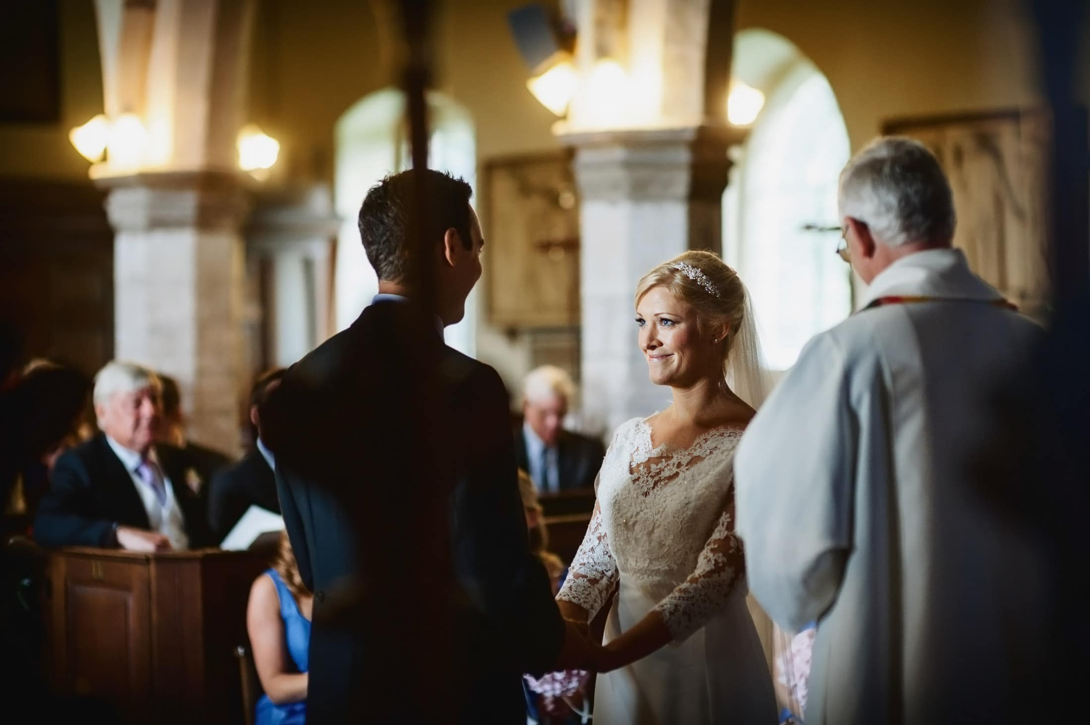 Bride smiling as groom reads wedding vows in church