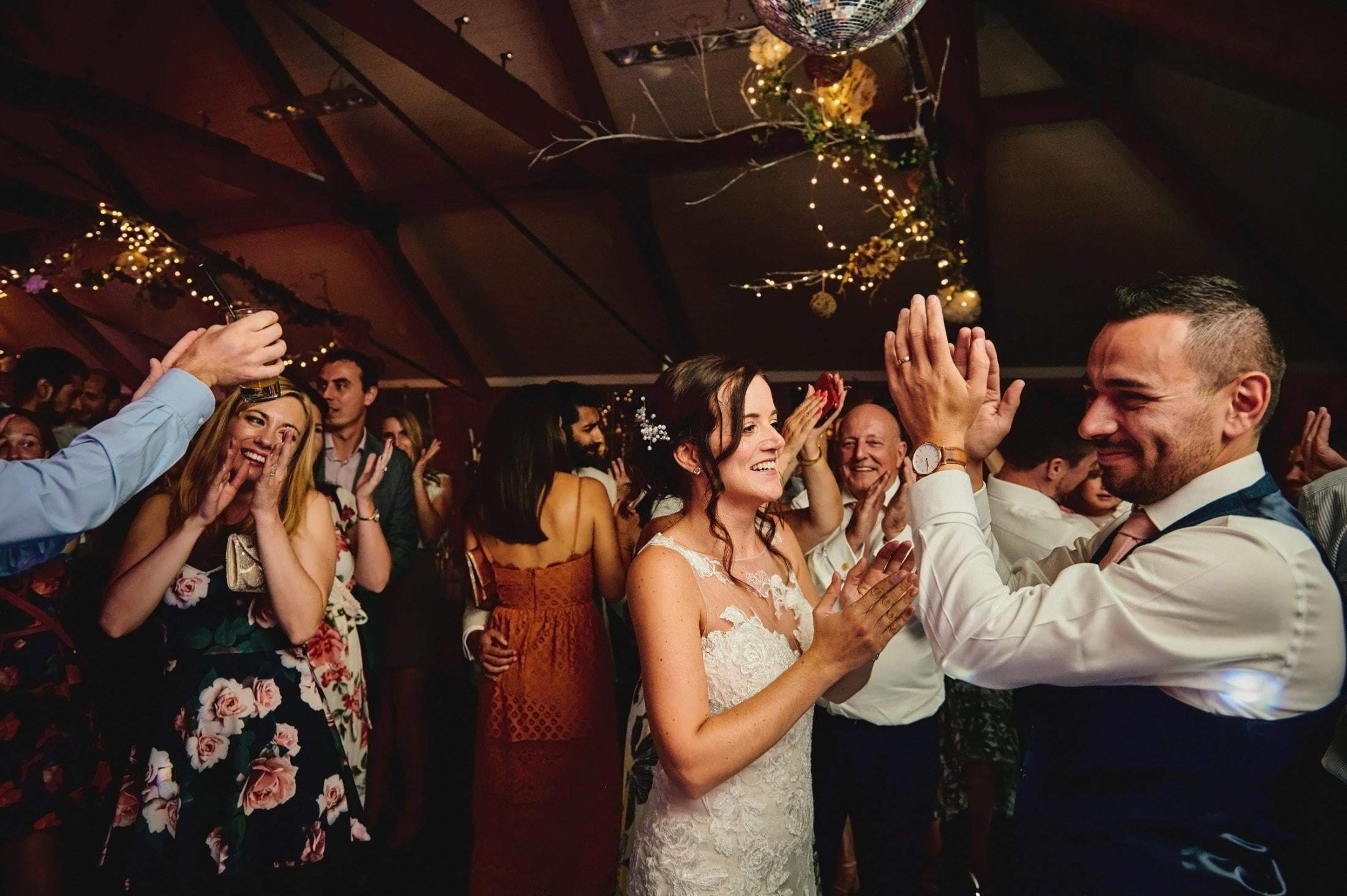 Bride, groom and wedding guests having fun on dancefloor