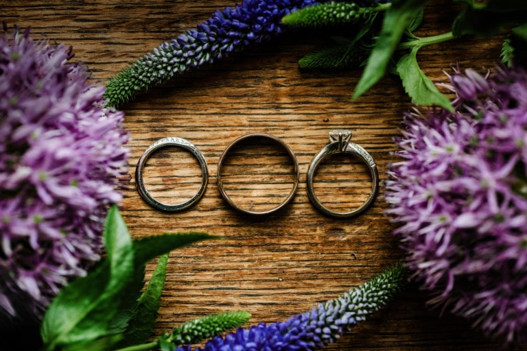 Detail of wedding rings surrounded by purple flowers