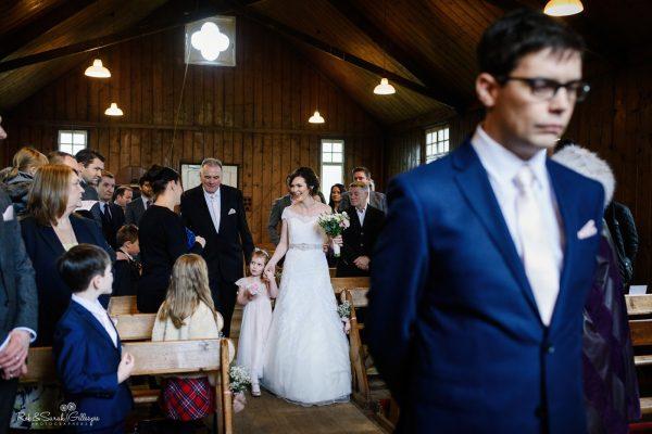 Groom waits as bride enters wedding ceremony in old chapel