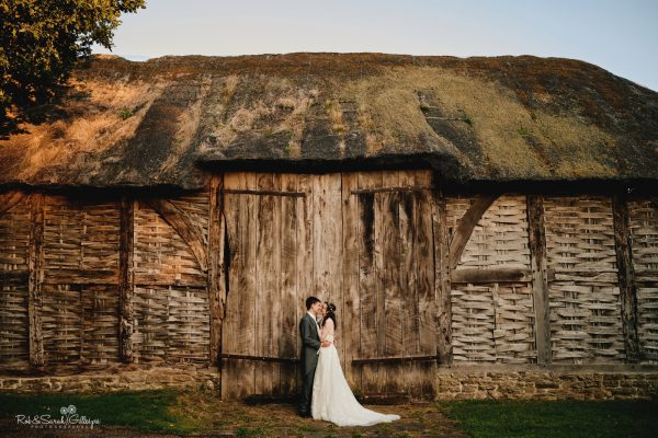 Bride and groom together in front of old threshing barn at Avoncroft Museum