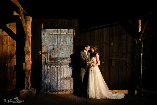 Bride and groom in front of old building at Avoncroft with strong evening light