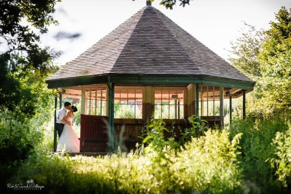 Newly married couple kissing under old shelter at Avoncroft Museum