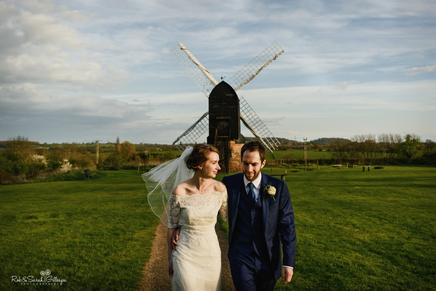 Bride and groom walking away from old windmill at Avoncroft Museum